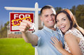Military couple in front of home house keys and sign mixed race excited new with new sold real estate outside Stock Photos