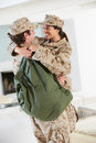 Military couple greeting each other on home leave hugging and Royalty Free Stock Images