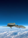Military drone strike electronic warfare flying above the clouds through a blue sky war has changed with new weapon technology Stock Image
