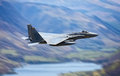 Military fighter jet an f strike eagle flying the mach loop aka the roundabout over tal y llyn lake wales Stock Image