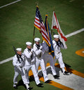 Military march with flags and rifles five uniformed navy men marching Stock Photos