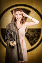 Military pin up woman atomic female bombshell old fashion photograph of a saluting with allied gas mask in front of a nuclear Royalty Free Stock Image