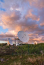 Military radar station at sunset multiple parabolic antenna on a surveillance compound Stock Images