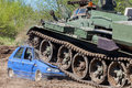 Military tank crushes a blue car Royalty Free Stock Photo