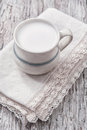Milk in ceramic mug on the lace napkin and the old wood background Stock Photos