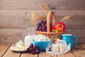 Milk, cheese and fruit basket over wooden background. Jewish holiday Shavuot celebration Royalty Free Stock Photo