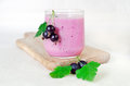 Milk cocktail of black currant berries and oat flakes in a glass cup on a wooden board. Decorated with black currant berries. Royalty Free Stock Photo