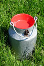 Milk container metal with on the green grass field Stock Photo