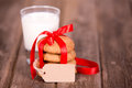 Milk and cookies glass of a stack of homemade tied with a red ribbon a gift tag with space for your text over old wooden Stock Photos