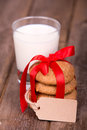 Milk and cookies glass of a stack of homemade tied with a red ribbon a gift tag with space for your text over old wooden Stock Photo