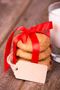 Milk and cookies glass of a stack of homemade tied with a red ribbon a gift tag with space for your text over old wooden Royalty Free Stock Images