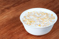 Milk and cornflakes in a white bowl on a wooden table