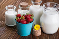 Milk in glass container and a bucket of strawberries on wooden table Stock Images