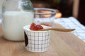 Milk ice cream in white cup with Spoon of strawberry jam on top Royalty Free Stock Photo