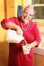 Milk its good for you a senior gray haired granny lady with laughing expression wearing cat eye glasses pearls and curlers in her Royalty Free Stock Photos