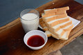 Milk jam and slices of bread Stock Images