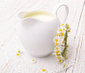 Milk jug in white on a white wooden table Royalty Free Stock Image