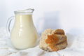 Milk in a milkman and a piece of bread are on the white cotton napkin Royalty Free Stock Photography