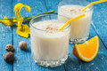 Milk and orange cocktail with nutmeg freshly prepared in a glass a slice of flower on a blue wooden table Stock Images