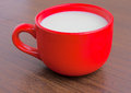Milk is poured into a ceramic mug red Stock Photos
