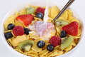 Milk pouring into fruit muesli with strawberries raspberries kiwi and blueberries Royalty Free Stock Image