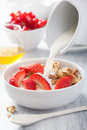 Milk pouring over granola strawberry breakfast Royalty Free Stock Photo