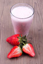 Milk shake with strawberry on a table Royalty Free Stock Images