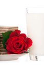 Milk with wafers and red rose for a romantic breakfast over white background Royalty Free Stock Images