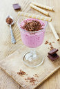 Milkshake with banana strawberry and black currant grated chocolate on a rustic wooden table Stock Image