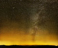 Milky way over black mountains and city lights Stock Image