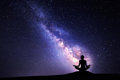Milky Way and silhouette of a woman practicing yoga. Royalty Free Stock Photo