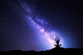 Milky Way and silhouette of a woman practicing yoga Royalty Free Stock Photo