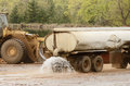 Mill ops large truck pulling a water tank spraying for dust control at a log yard at a lumber processing that specializes in small Stock Images