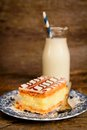 Millefeuille french pastry with custard and bottle of milk with a blue straw on a wooden table Royalty Free Stock Image
