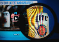Miller lite photo of homepage on a monitor screen through a magnifying glass Royalty Free Stock Photography