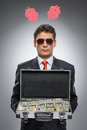 Millionaire. Confident man in formal wear holding a suitcase ful Royalty Free Stock Photo