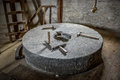 Millstone with tools big old on it Royalty Free Stock Image