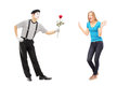 Mime artist giving a rose flower to an excited woman full length portrait of women isolated on white background Royalty Free Stock Photos