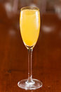 Mimosa sparkling wine served in a flute with fresh orange juice on a out of focus bar top Stock Photo