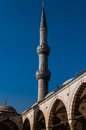 Minaret of a mosque historical against blue sky on the background in bright day Royalty Free Stock Photography