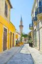 The minaret narrow street with small outdoor cafe and of grand mosque cami kebir on background limassol cyprus Stock Photography