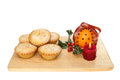 Mince pies on a board with decorated orange and holly isolated against white Royalty Free Stock Image