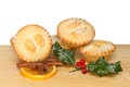 Mince pies on board a wooden with holly orange cinnamon and star anise Stock Photo