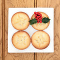 Mince pies christmas pie cakes and holly on a plate over oak background Stock Images