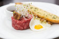 Minced beef tartare style close up of with fried egg chanterelle and garlic bread Stock Photos