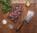 Minced lamb on a cutting board with a meat cleaver, herbs and spices on wooden rustic background top view close up Royalty Free Stock Photo