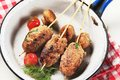 Minced meat kebabs and mushrooms in a pan Stock Images