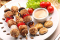 Minced meatballs baked as skewers with dip and mushrooms on whit white plate Royalty Free Stock Photography