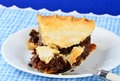 Mincemeat pie in country setting bite cut from flaky crust of old fashioned on fork on blue gingham place mat Stock Image