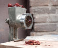 Mincing machine and cherry berries ripe red cherries in a meat grinder on a background of an old brick wall Stock Images